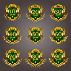 Set of gold anniversary badges with laurel wreaths, shield, numbers. Decorative emblem of jubilee on gray background. Filigree element, frame, border, icon, logo for web, page design in vintage style