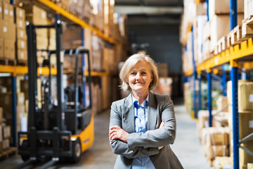 Senior woman warehouse manager or supervisor , arms crossed.