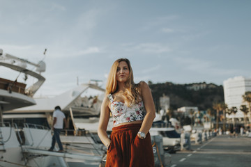 Blonde young woman posing in the marina port of Malaga city, looking at camera, with yachts and boats docked in the background.
