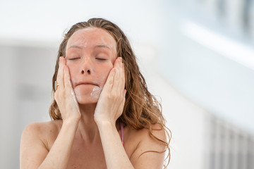 Happy smiling wavy hair woman Applying Sunscreen Suntan Lotion on her face, skin care protection concept.