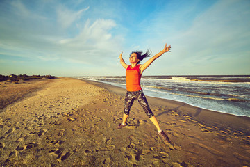 Happy smiling woman jumping on the beach.