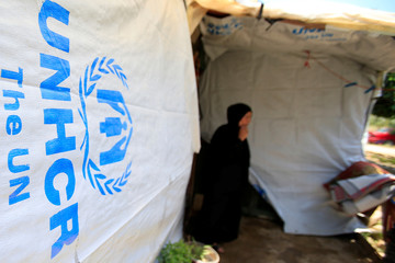A Syrian refugee woman stands outside a tent at a refugee camp in Zahrani town
