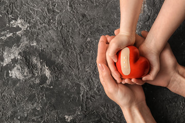 Hands of mother and child holding red heart with plaster on dark background. Health care concept