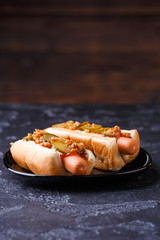 Photo of hotdogs on black plate
