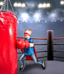 A child in a superhero costume athlete boxer. Boxer is hitting a boxing  bag in the gym.