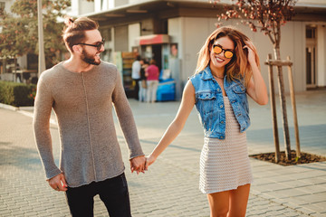 Couple holding hands and walking on the sidewalk