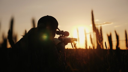 Poster Chasse A sniper rifles from a rifle with an optical sight. On the Sunset. Sports shooting and hunting concept