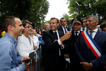 French President Emmanuel Macron makes a selfie with people as he arrives to lay a wreath at the tomb of Georges Clemenceau in Mouchamps in Vendee