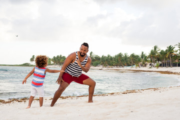 Ethnic man playing with son on beach