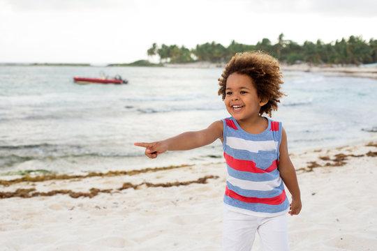 Ethnic boy pointing away on beach