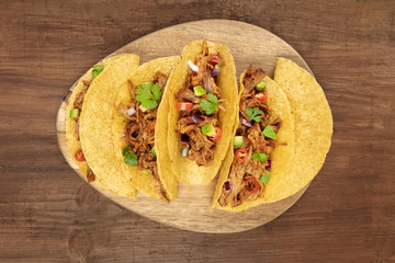 Overhead photo of Mexican tacos with pulled pork, avocado, chili peppers, cilantro, with place for text