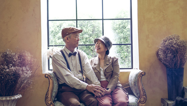 Asian senior couple smiling dress vintage retro style in luxury house with tuscan style yellow wall