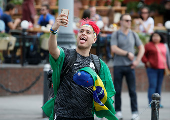 A supporter of the Brazilian national soccer team takes a selfie in a street on the eve of the 2018 FIFA World Cup in central Moscow