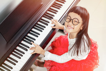 Little asian girl very happy to play piano