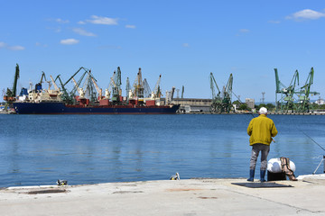 Varna Harbour, Bulgaria. Elderly fisherman fishing on the pier. Cranes and freighters seen at background.