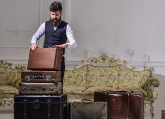 Man, traveller with beard and mustache packing luggage before trip, luxury interior background. Luggage and travelling concept. Macho elegant on thoughtful face standing near pile of vintage suitcase.