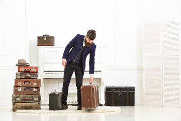 Macho elegant on strict face stands near pile of vintage suitcase, ready for vacation. Man, traveller with beard and mustache with luggage, luxury white interior background. Luggage and travel concept