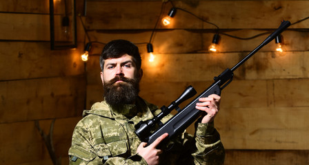 Man with beard wears camouflage clothing in wooden interior background. Macho on strict face at gamekeepers house. Gamekeeper concept. Hunter, brutal hipster with gun in his hand ready for hunting.