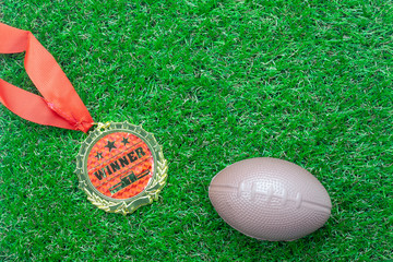 Table top view aerial image soccer or football season background.Flat lay accessories gold medal & american ball on the artificial green grass wallpaper.Free space for design text and content.