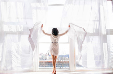the young woman stands on the window among the open curtains