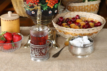 A glass of black tea, samovar and summer berries and fruits.