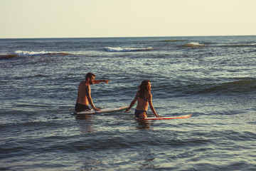 Man and woman surfers chasing waves