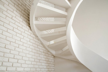 a wall of white brick and a spiral staircase in the house