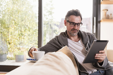 Portrait of mature man with cup of coffee sitting on couch using tablet