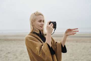 Netherlands, portrait of blond young woman with camera on the beach