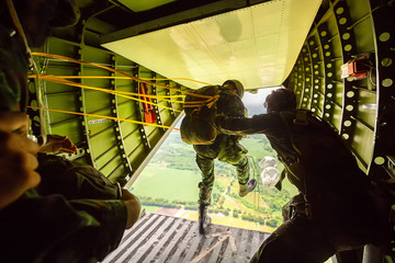 Foto auf Acrylglas Luftsport Rangers parachuted from military airplanes, Soldiers parachuted from the plane, isolated airborne soldier, practice parachuting, Paratroopers jumping from an airplane.