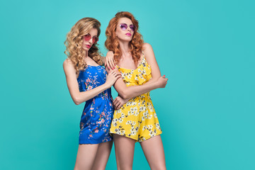 Wall Mural - Two Young Woman in Fashion pose. Trendy Floral Dress, Wavy Hairstyle. Glamour Sexy Blond Redhead Model in Stylish Sunglasses. Playful Summer Slim Girl on Blue