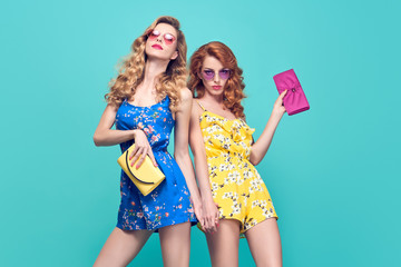 Wall Mural - Two Young Woman in Fashion pose. Trendy Floral Dress, Wavy Hairstyle. Glamour Sexy Blond Redhead Model in Stylish Sunglasses, Clutch. Playful Summer Slim Girl on Blue