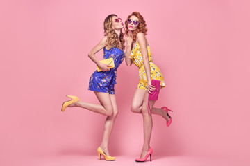 Wall Mural - Two Young Woman Having Fun Blowing lips. Trendy Floral Dress, Wavy Hairstyle. Glamour Sexy Blond Redhead Model in Stylish Summer Sunglasses, Clutch. Playful Slim Girl on Blue