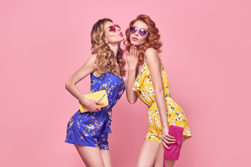Wall Mural - Two Girls Having Fun. Kiss Face Expression. Trendy Floral Dress, Wavy Hairstyle. Young Pretty Woman in Stylish Summer Sunglasses. Playful Beautiful Sisters Twins on Pink
