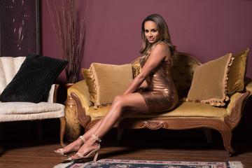 Elegant Woman in a Bronze Dress Sitting on a Vintage Sofa