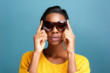 trendy young black woman in sunglasses by blue wall