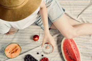 summer picnic setting. Woman in jean shorts and hat eatining water melon, melon, blueberries, raspberries and peaches, drinking water. Outdoor gathering concept.