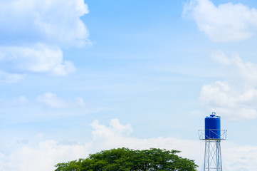 A plastic blue water tank on the tower in park