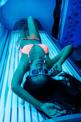 beautiful slender girl in a swimsuit and sunglasses sunbathing under the ultraviolet rays