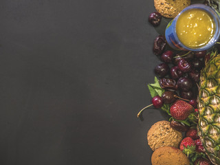 overhead strawberries pineapple orange cookies and cherry with dates copy space flat lay