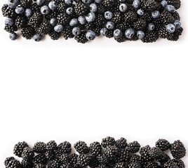 Black and blue berries on a white. Top view. Ripe blackberries and blueberries on white background. Berries at border of image with copy space for text.