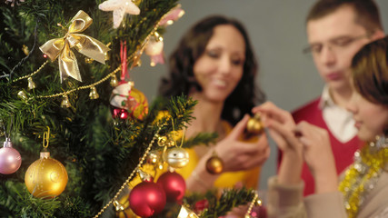 Loving parents helping their daughter to decorate Christmas tree, magic moments