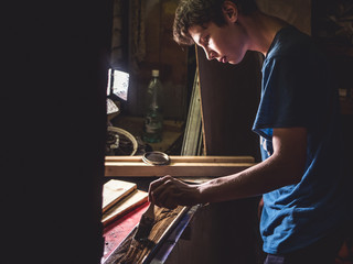portrait of young man craftsman working with paintbrush with wooden surface