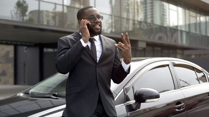 Afro-American man in expensive business suit talking over phone on parking lot