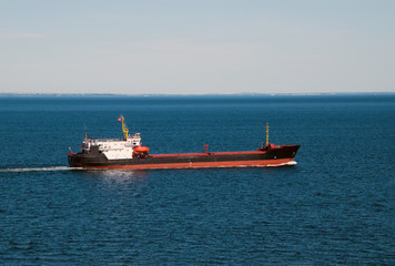 Red white and black tanker ship in the deep blue water of the Baltic Sea between Germany and Denmark