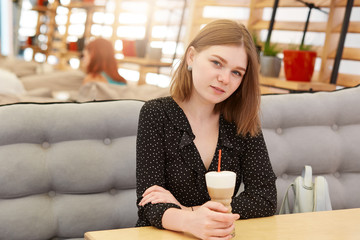 Pretty European female drinks milk shake in cafe, wears black stylish polka dot blouse, enjoys recreation time with friends. Beautiful woman has cocktail at cozy outdoor restaurant, has happy look