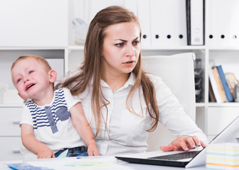 Girl is working with a naughty child in her arms behind a laptop