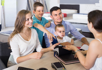 joyous family of four choosing fabric for upholstery mattress in salon