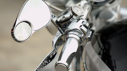 Close-up of motorcycle control panel with speedometer and handles, dashboard