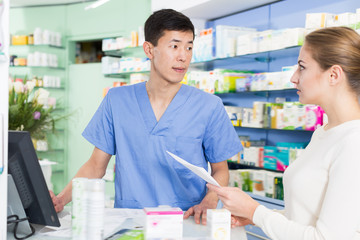 Young woman is asking pharmacist about medicines